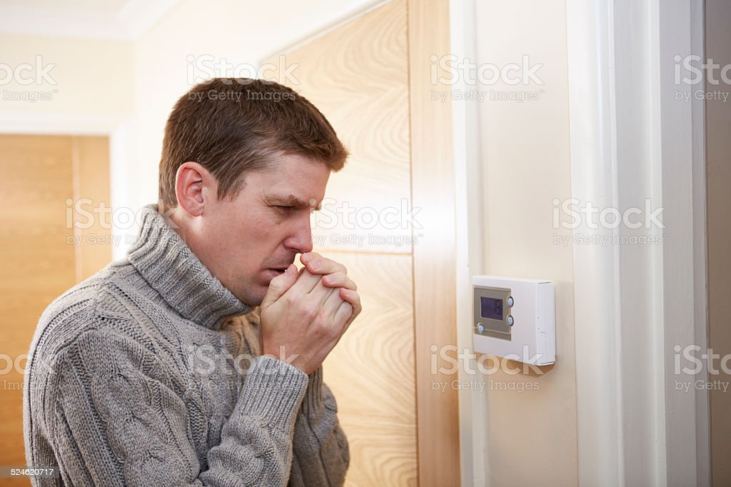 Man feeling cold checking digital thermostat stock photo