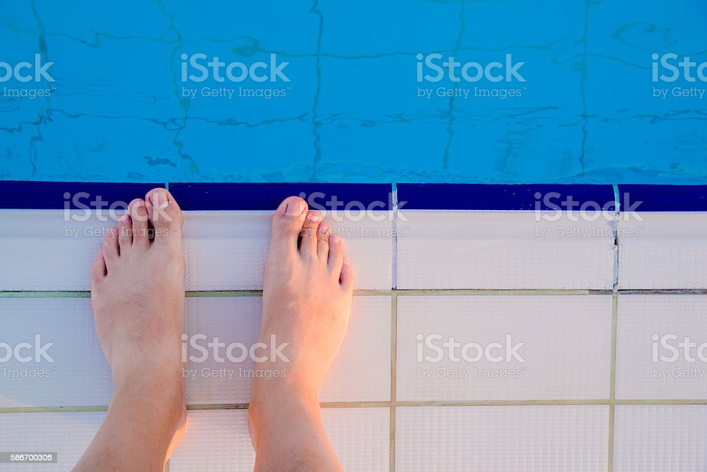 Man feet at the swimming pool stock photo