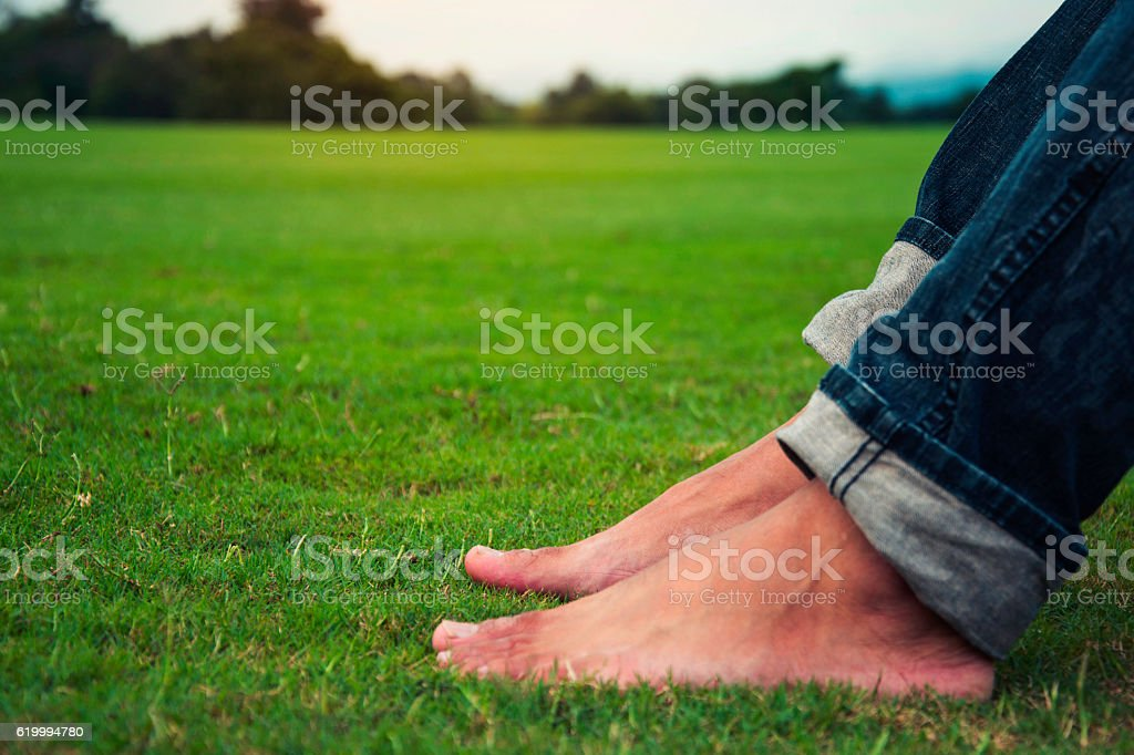 Man feet relaxing on grass enjoying in a day in a royalty-free stock photo