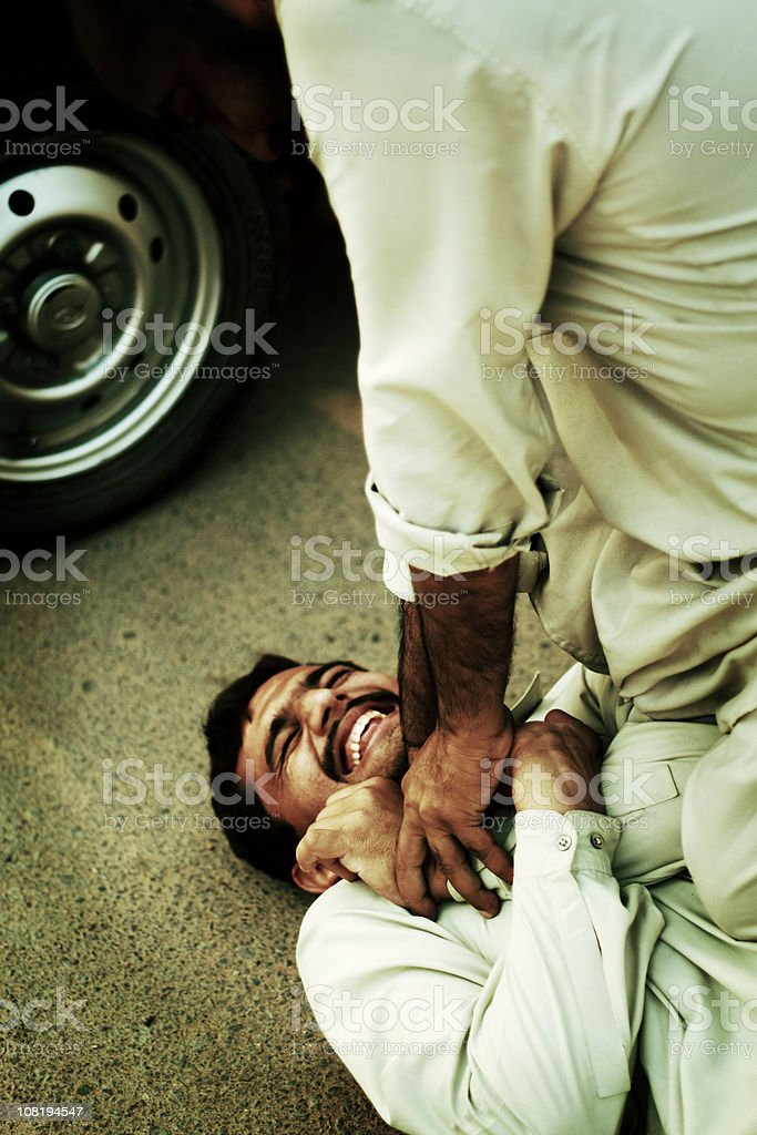Man Fighting and Holding Other Male on Ground stock photo