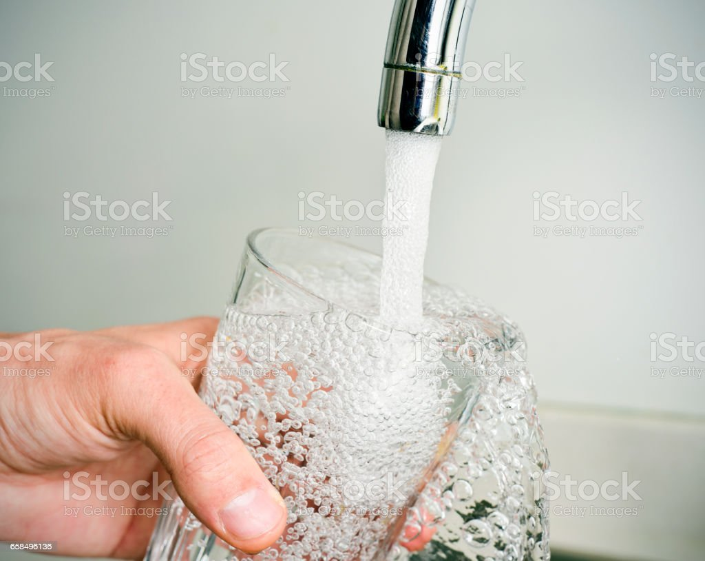 man filling a glass of tap water stock photo