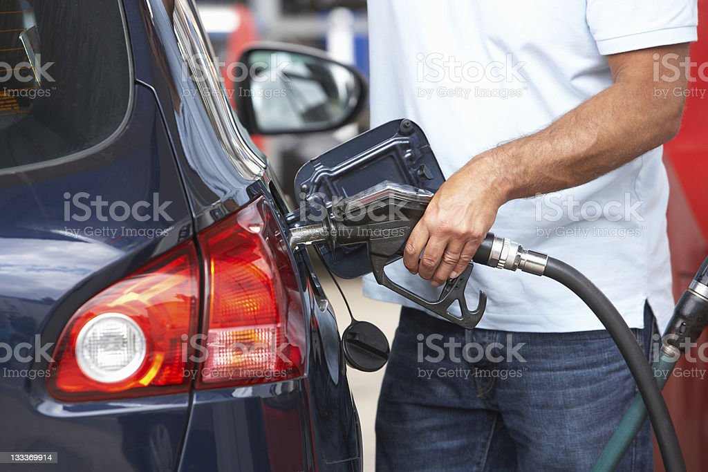 Man filling blue car with gasoline at gas station stock photo