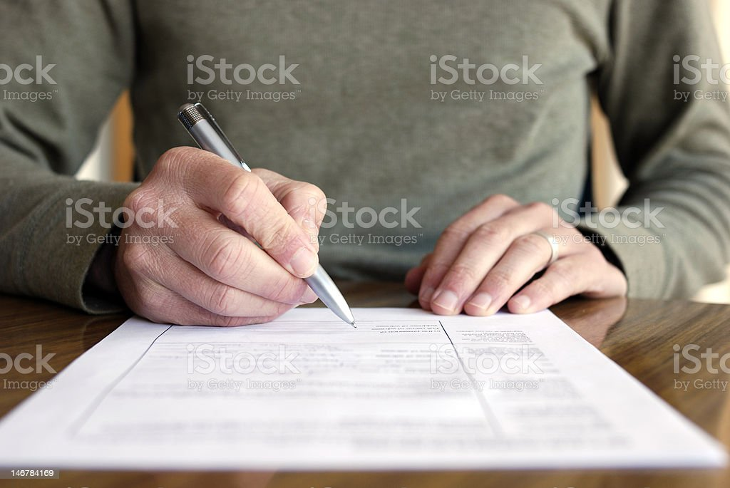 Man Filling Out Form on Table stock photo