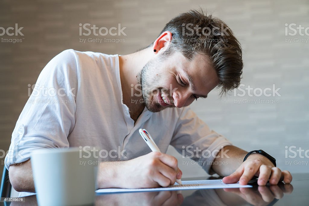 Man filling out important paper documents stock photo