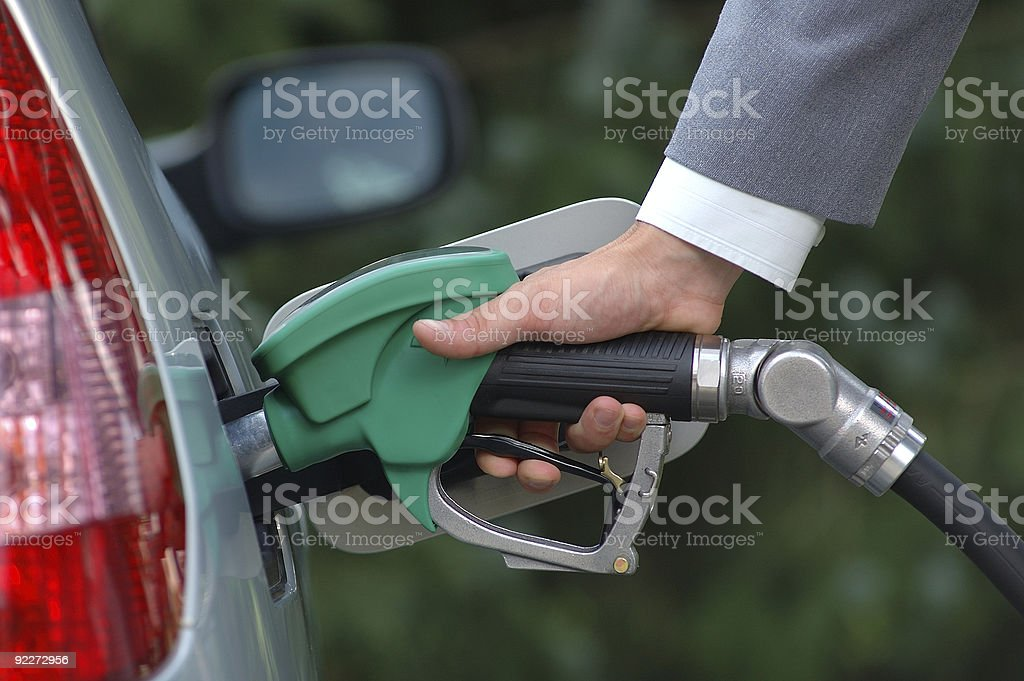 Man filling up silver car with green gas pump stock photo