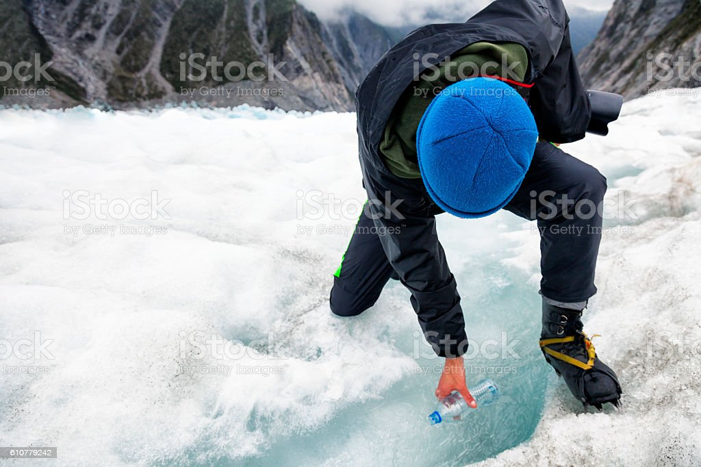 Man filling water bottle from stream on Franz Josef Glacier stock photo