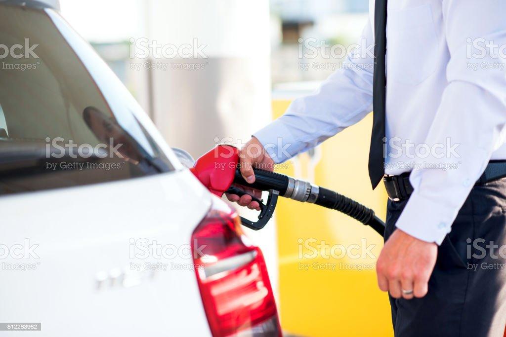 man fills a car with petrol stock photo