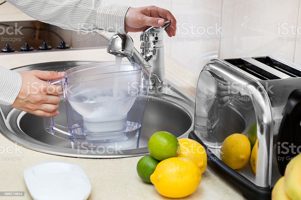 Man fills filter jug with tap water stock photo