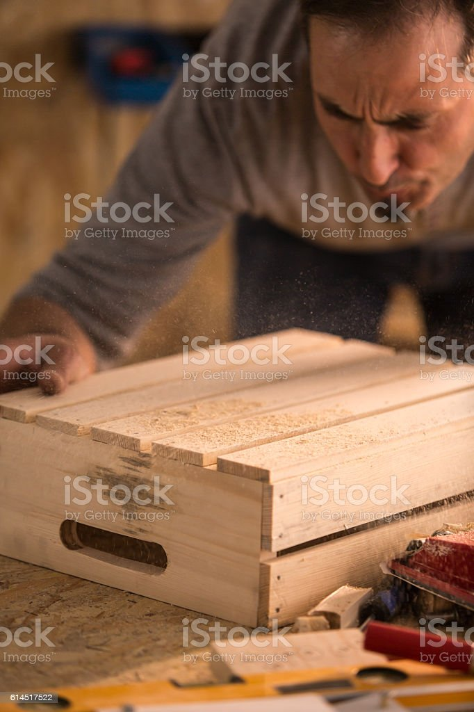 Man finishing wooden product in workshop stock photo