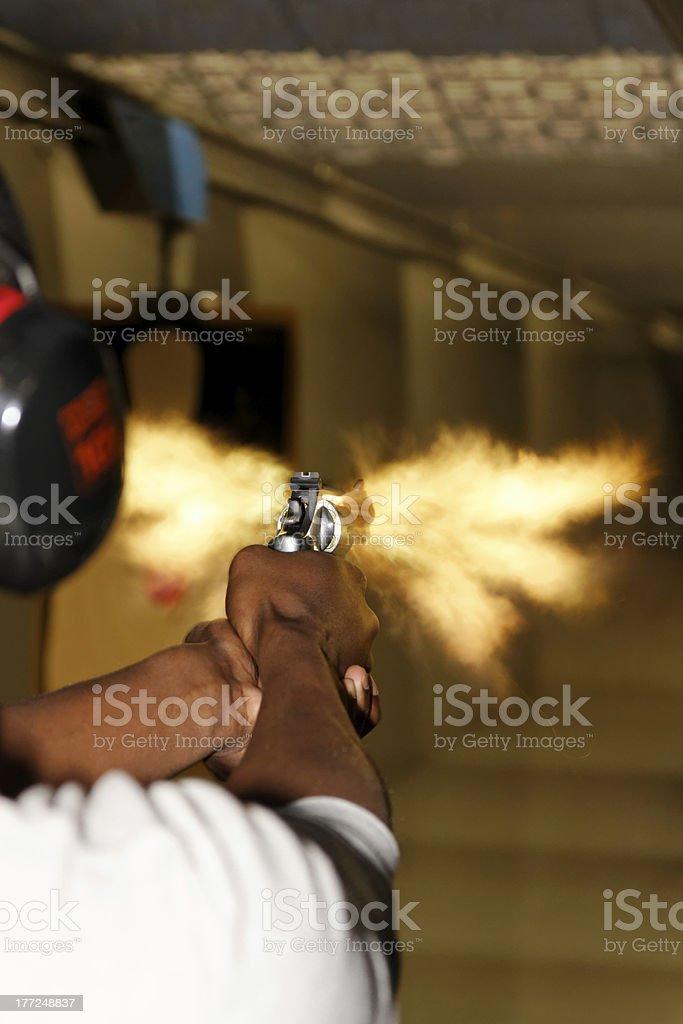 Man Firing Revolver Gun with Muzzle Flash stock photo