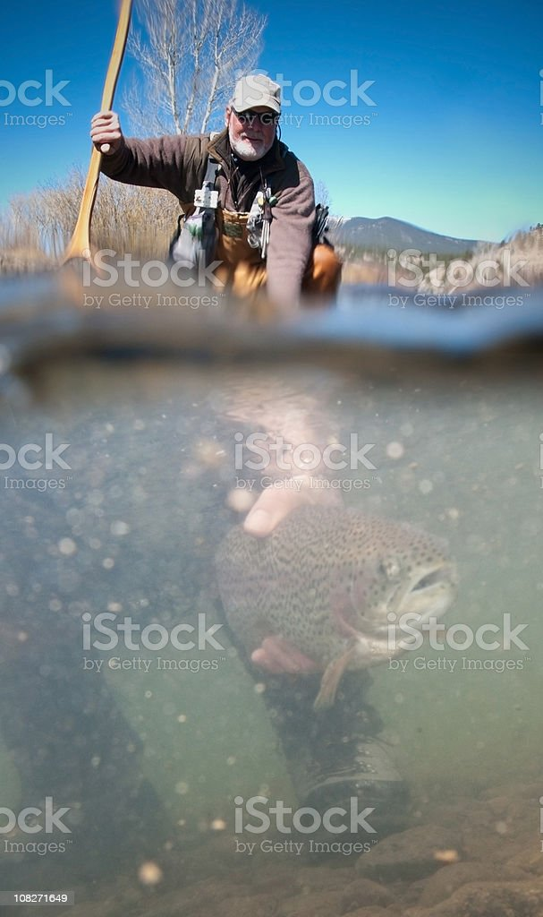 Man Fishing and Releasing Fish stock photo