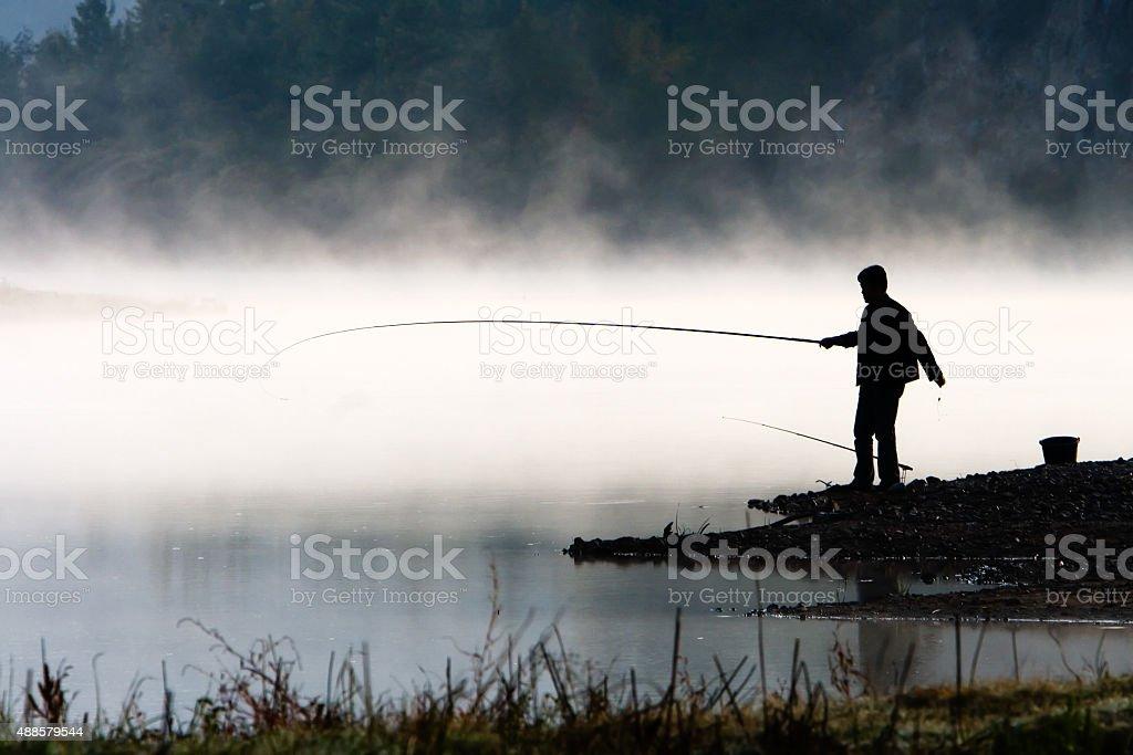 Man fishing at river shore stock photo