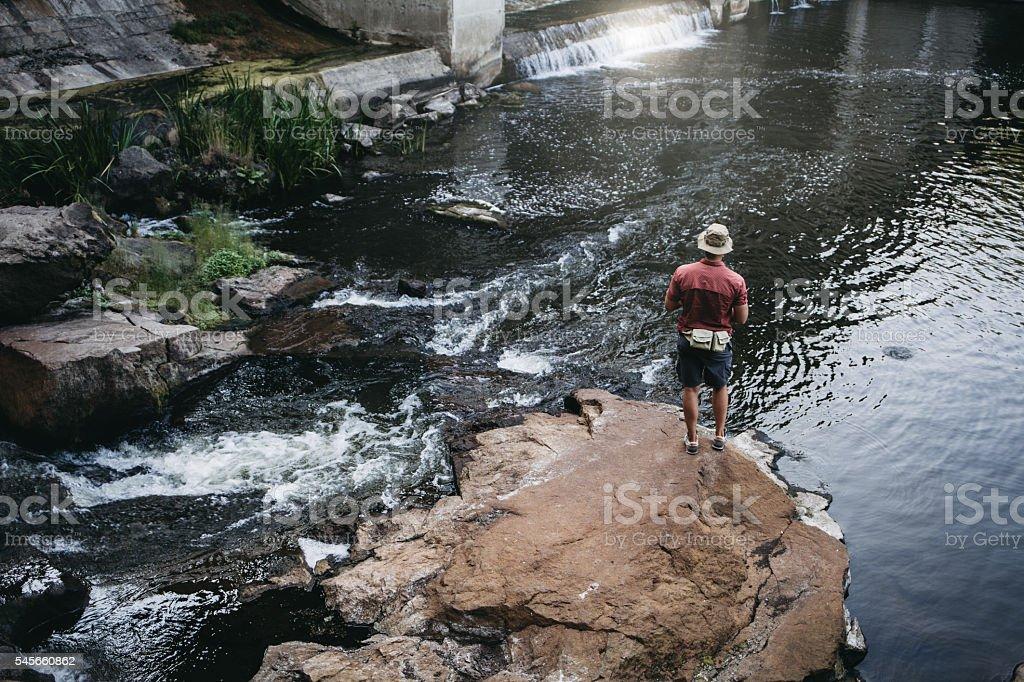 Man fishing, casting with ultralight rod near the dam stock photo