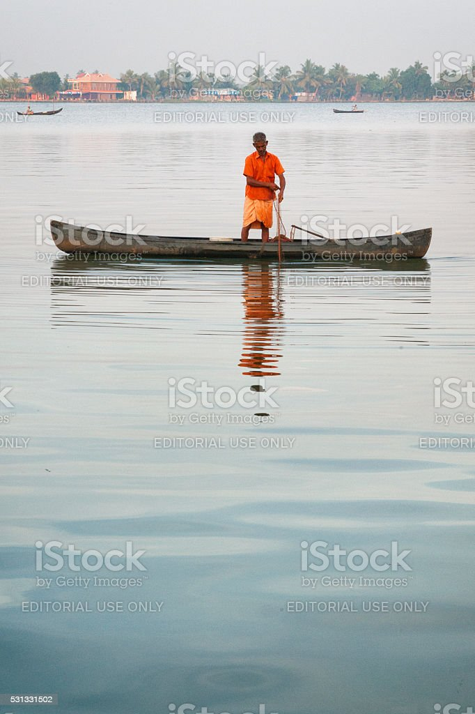 Man fishing from a Kettuvallam on Vembanad Lake, Kumarakom, India stock photo