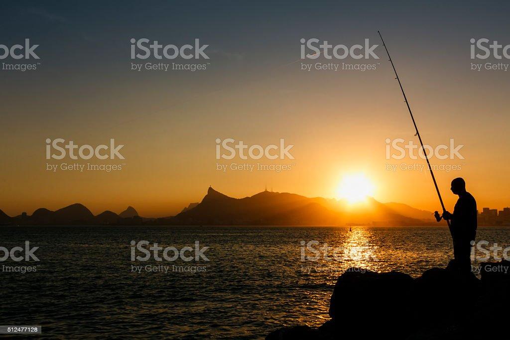 Man Fishing in Guanabara Bay at Sunset stock photo