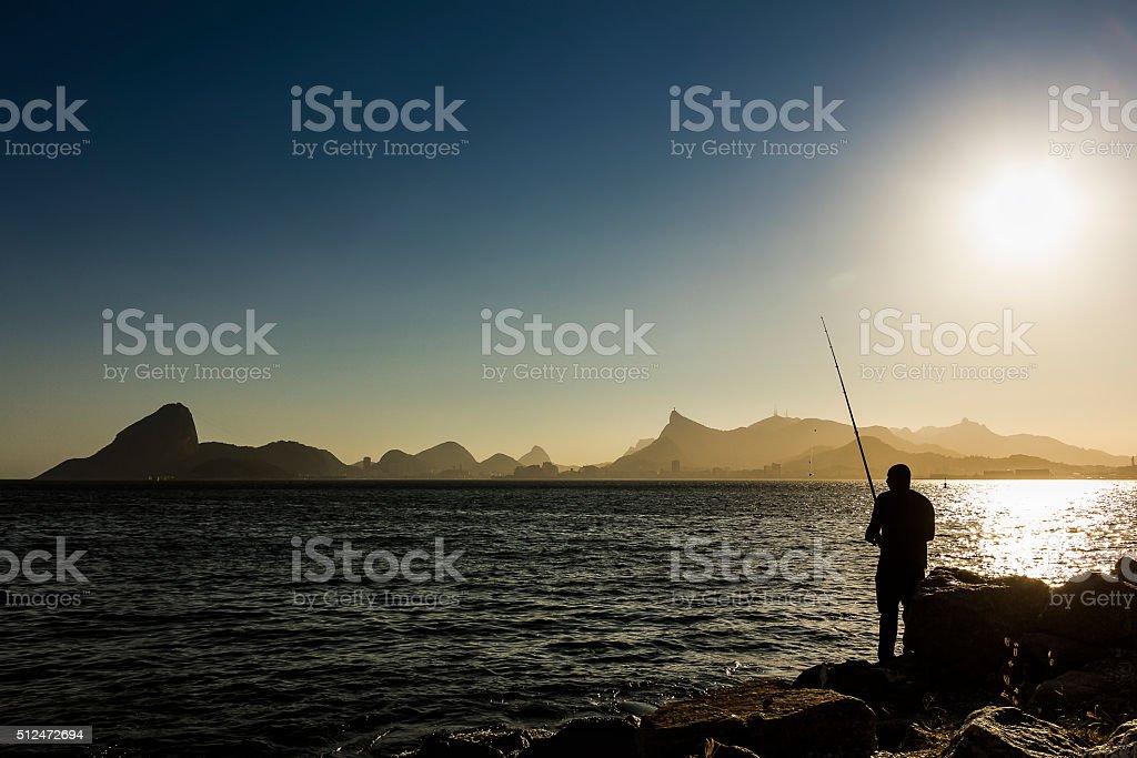 Man Fishing in Guanabara Bay near Sunset stock photo