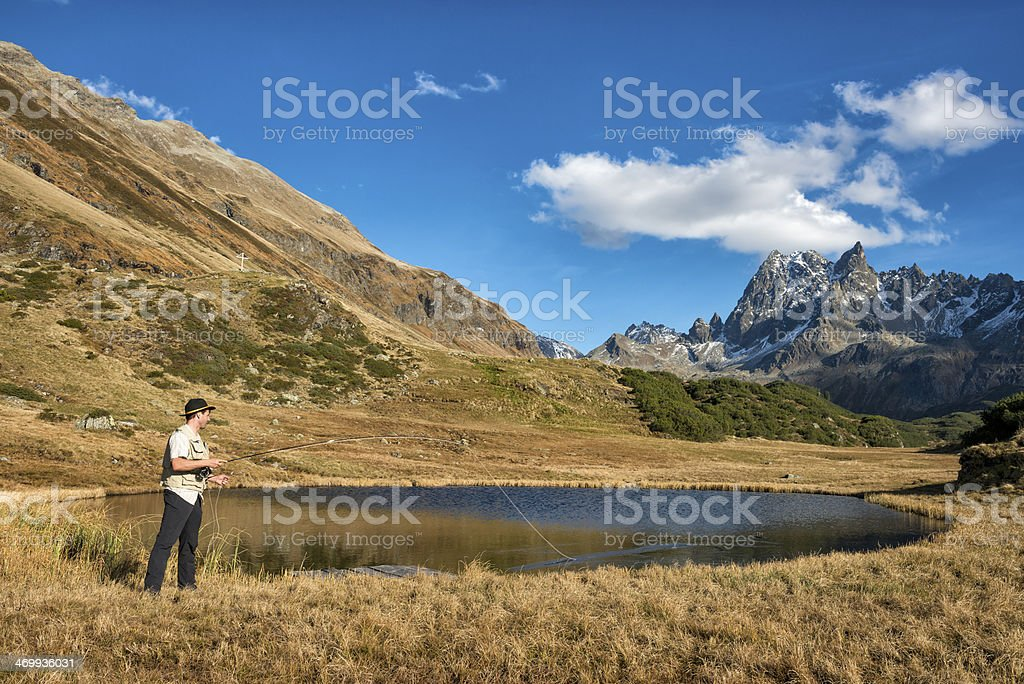 Man fishing in lake on sunny day royalty-free stock photo