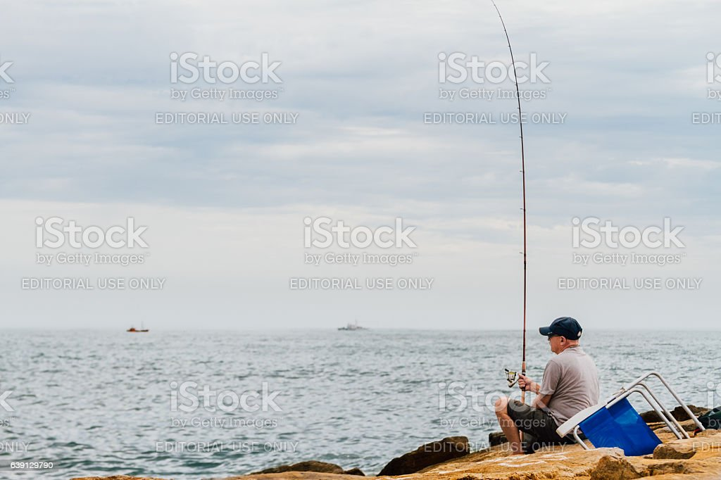 Man fishing on a breakwater of the Atlantic Ocean stock photo