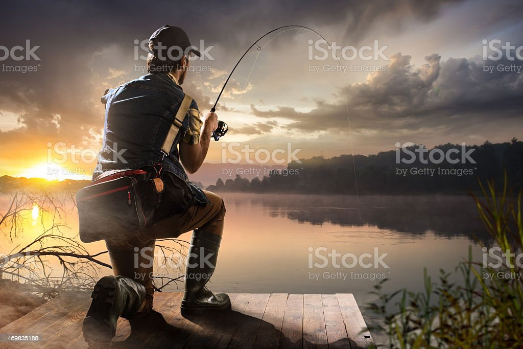 man fishing on a lake. Sunset