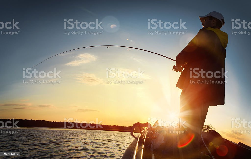 man fishing on a lake stock photo