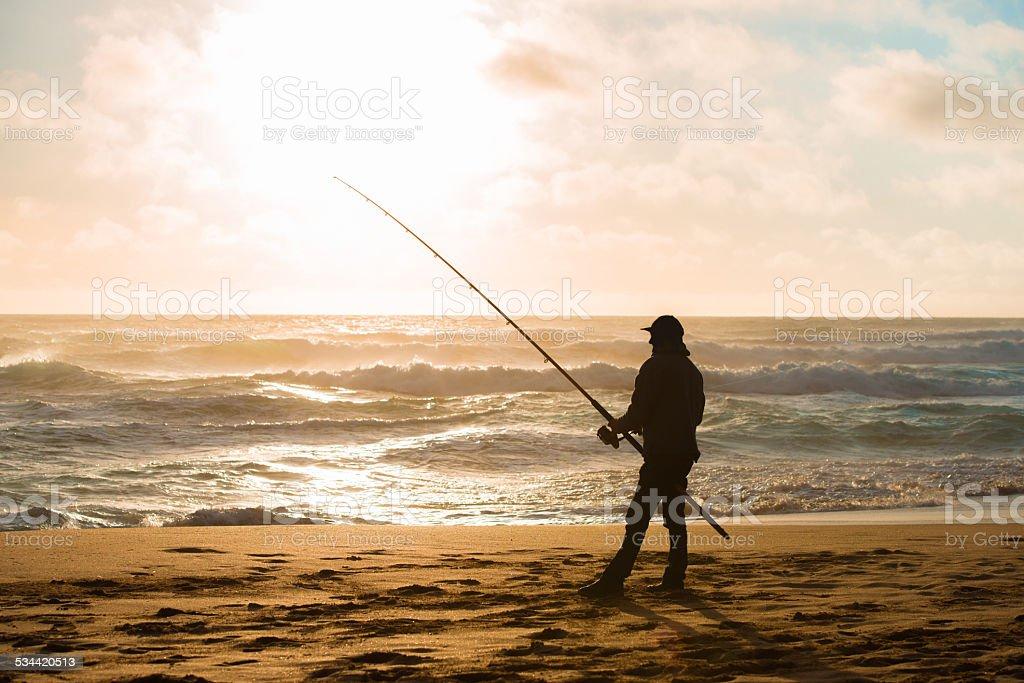 Man fishing on Beach at Sunset stock photo