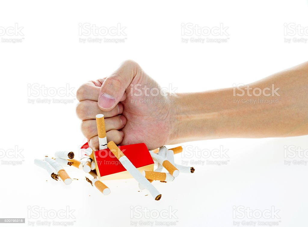 Man fist crushing cigarette pack stock photo