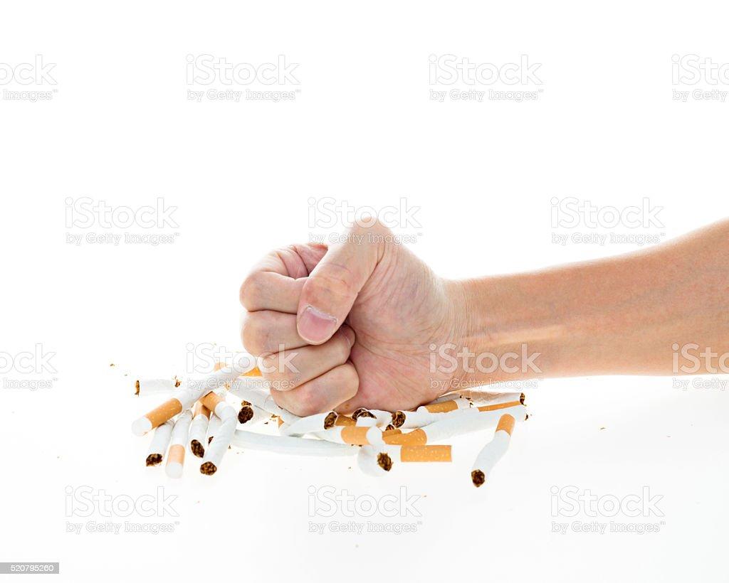 Man fist destroying cigarettes stock photo