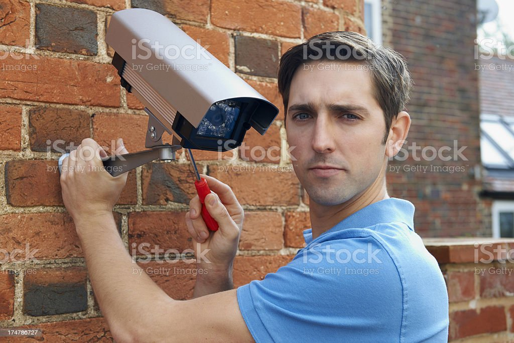 Man Fitting Security Camera To House royalty-free stock photo