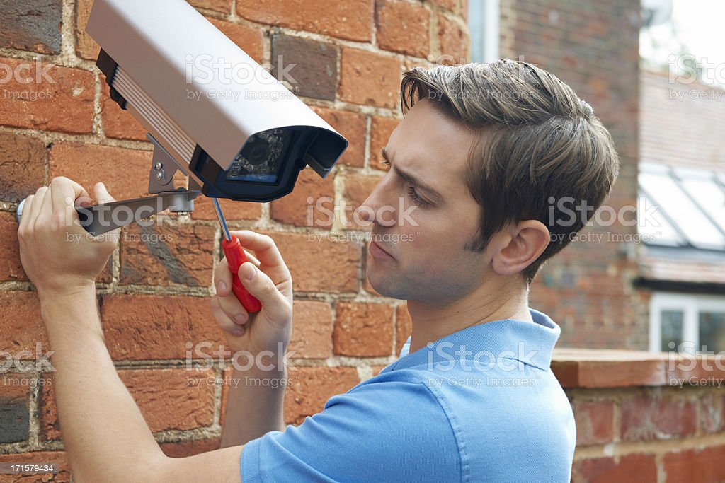 Man Fitting Security Camera To House Wall stock photo
