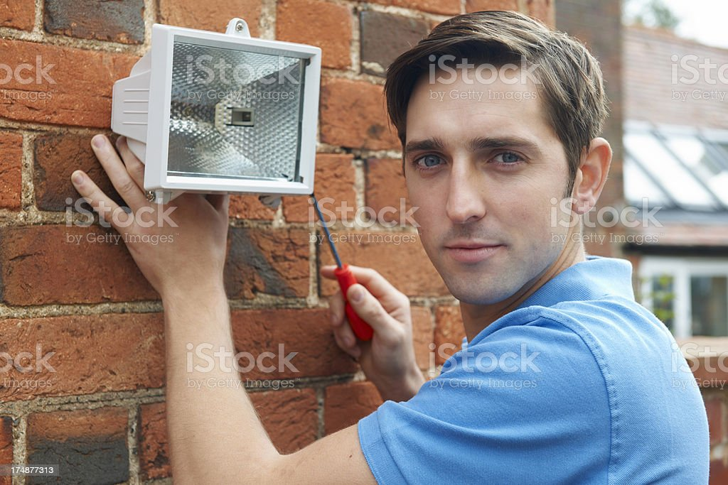 Man Fitting Security Light To Wall Of House royalty-free stock photo
