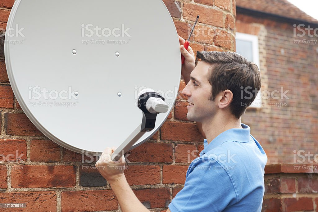 Man Fitting TV Satellite Dish To House Wall stock photo