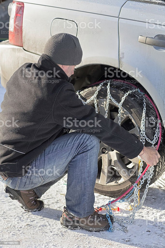 Man fitting tyre chains stock photo