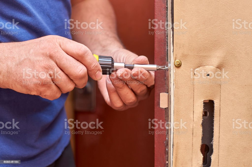 Man fixing a lock in old door stock photo