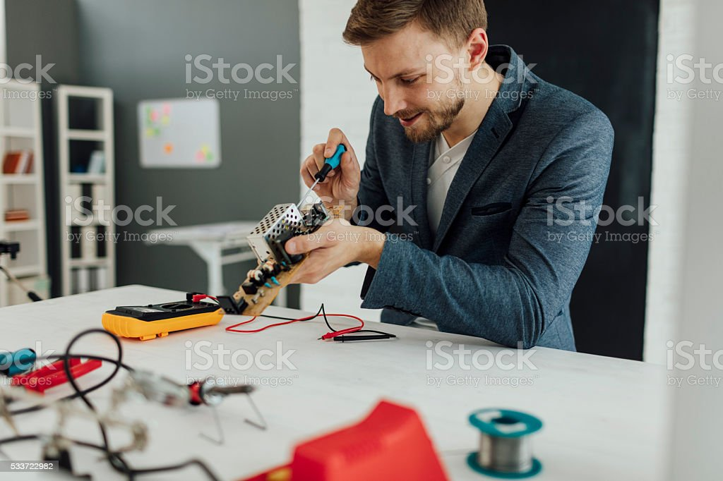 Man Fixing Circuit Board In His Office. stock photo