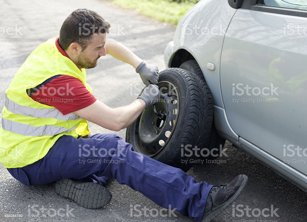 man fixing flat tire after a vehicle breakdown problem stock photo