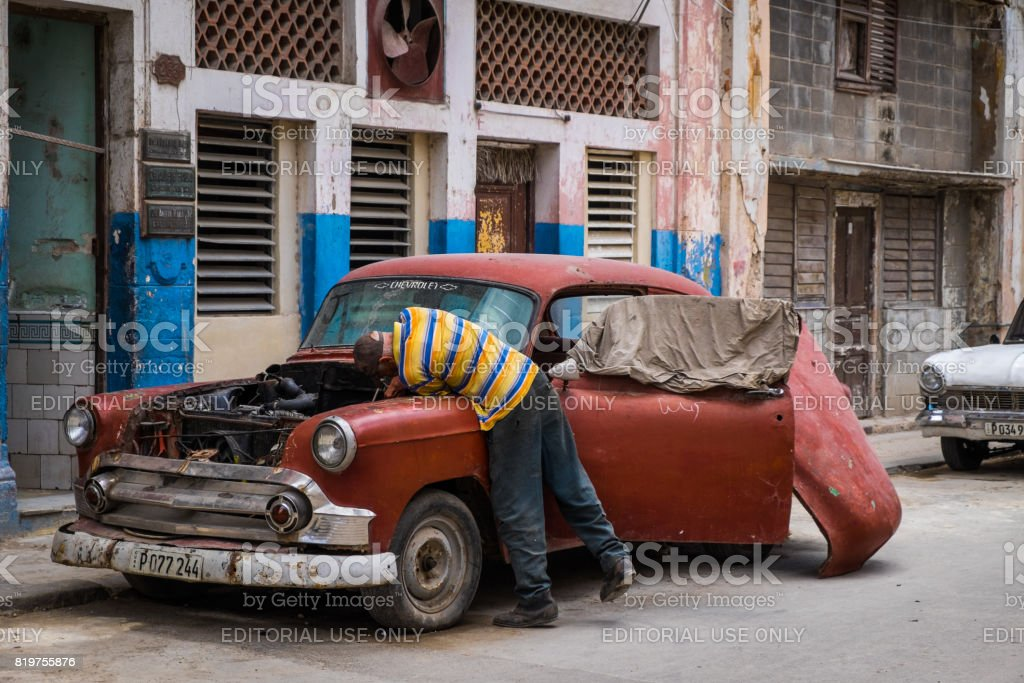 Man Fixing is car in the street of Havana, Cuna stock photo