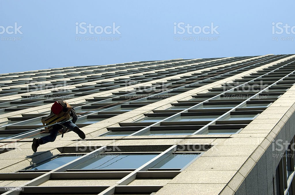 Man fixing windows on tall building stock photo