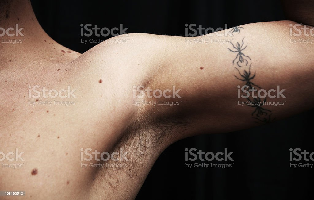 Man Flexing Arm Muscle with Tattoo royalty-free stock photo