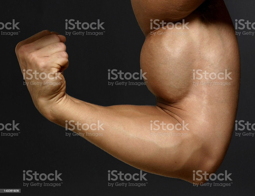 Man flexing his biceps and clenching his fist royalty-free stock photo