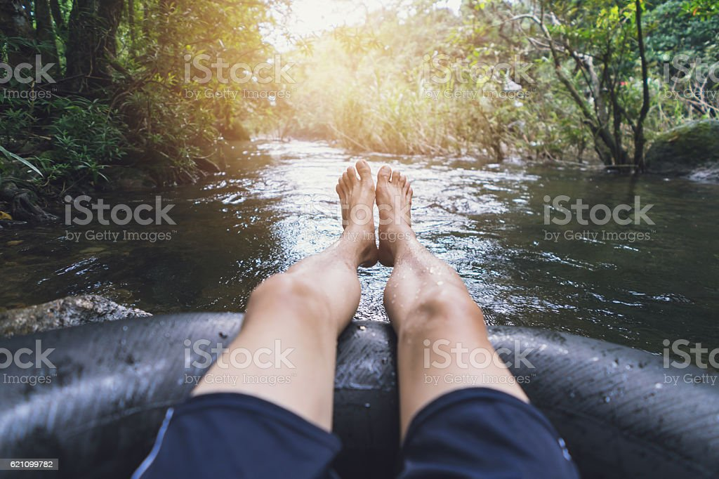 Man floating down a canal in a blow up tube stock photo