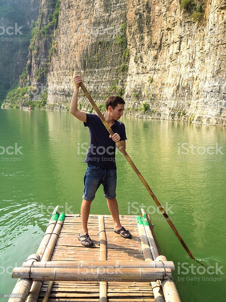 Man floating on a bamboo raft stock photo