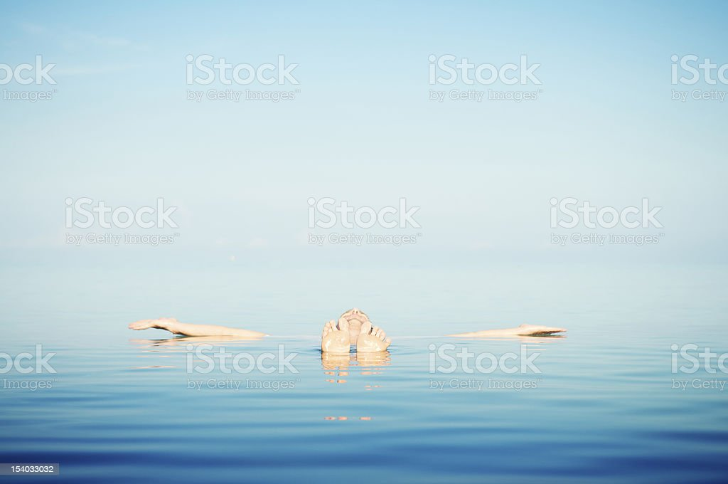 Man Floats in Tranquil Blue Waters stock photo