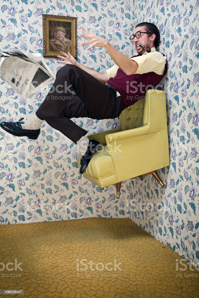 Man Floats Upward in Vintage Living Room Chair stock photo