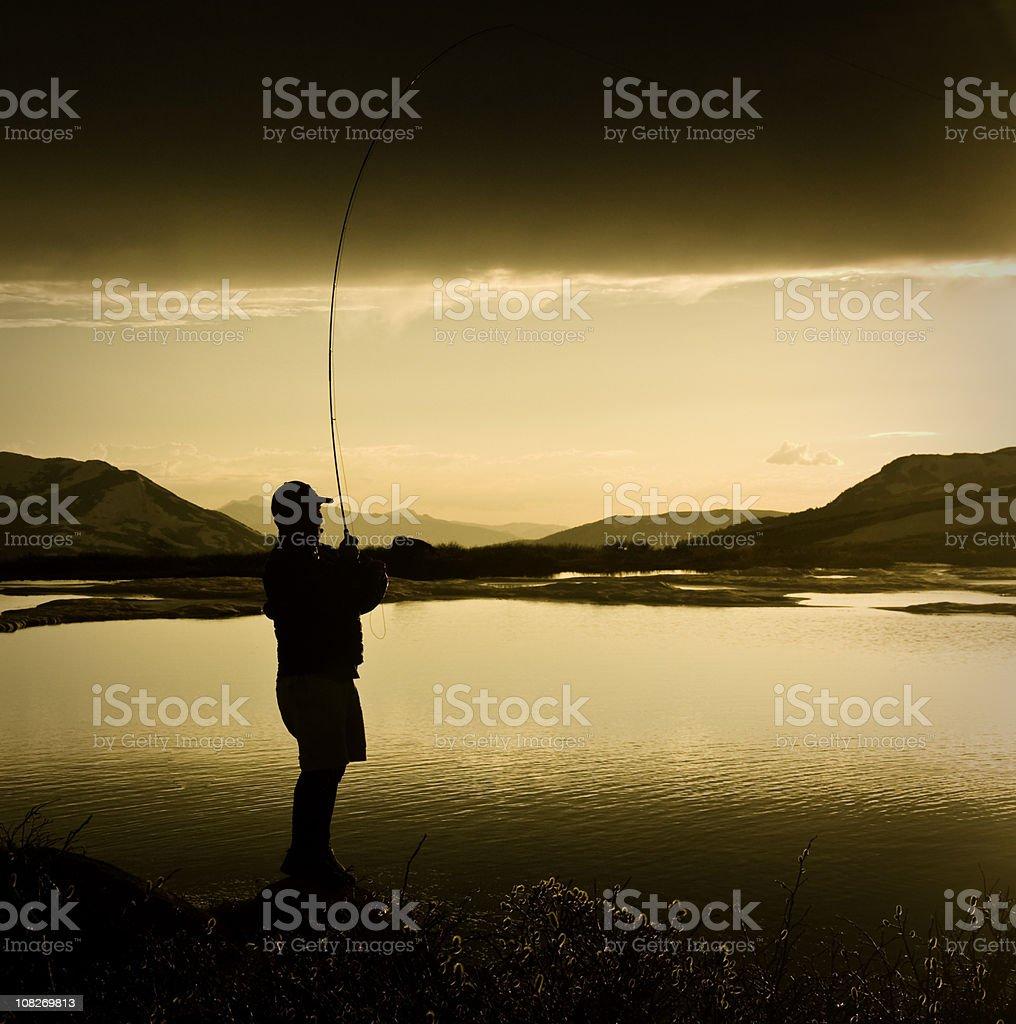 Man Fly Fishing at Sunset High Alpine Lake royalty-free stock photo
