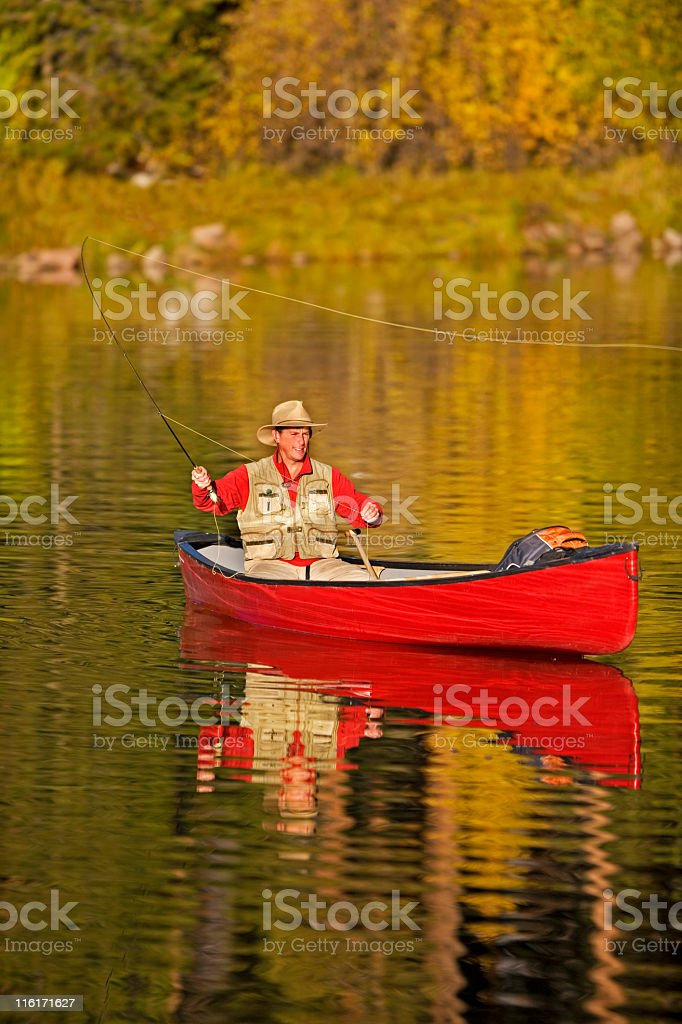 Man Fly Fishing From A Canoe In Colorado stock photo
