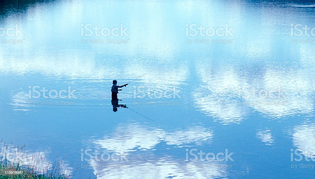 A man fly fishing in a cast amount of water royalty-free stock photo