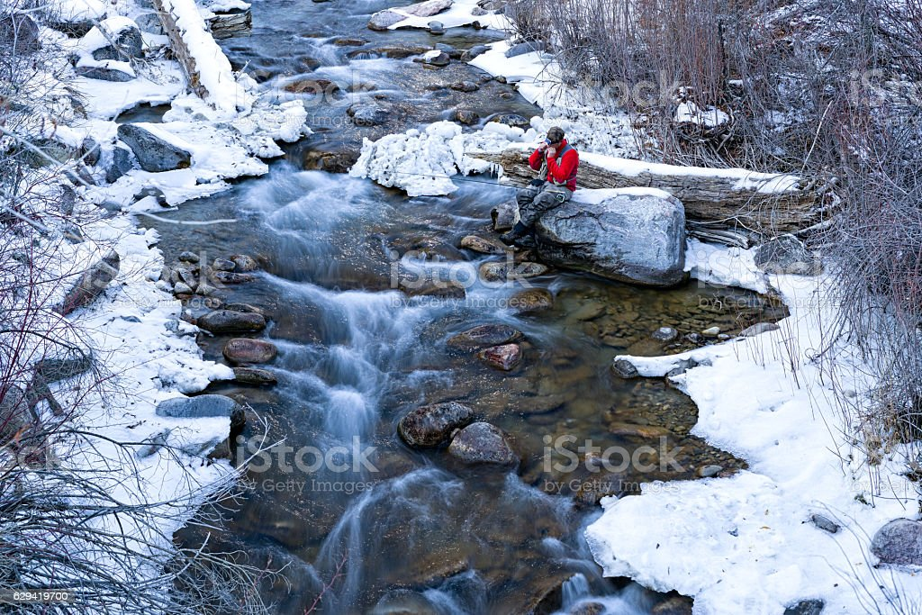 Man Fly Fishing Mountain Creek in Winter stock photo