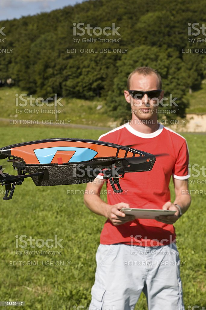 Man flying a drone with its touch pad stock photo