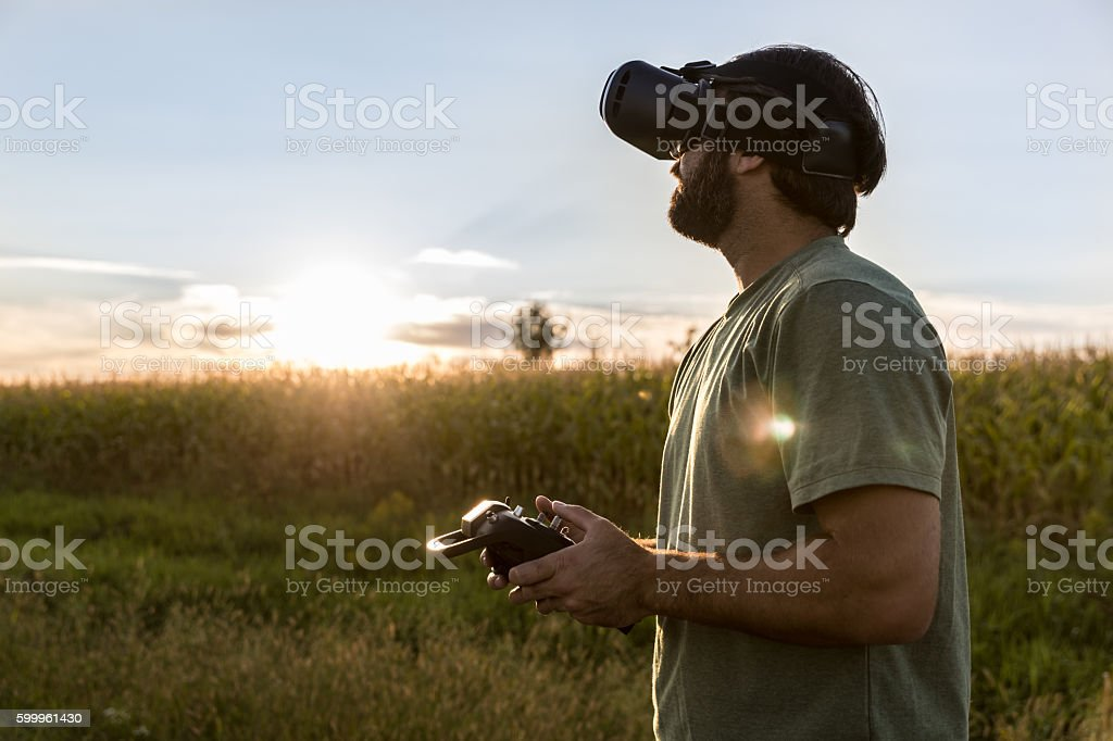 Man Flying a Drone with Virtual Reality Goggles Headset stock photo