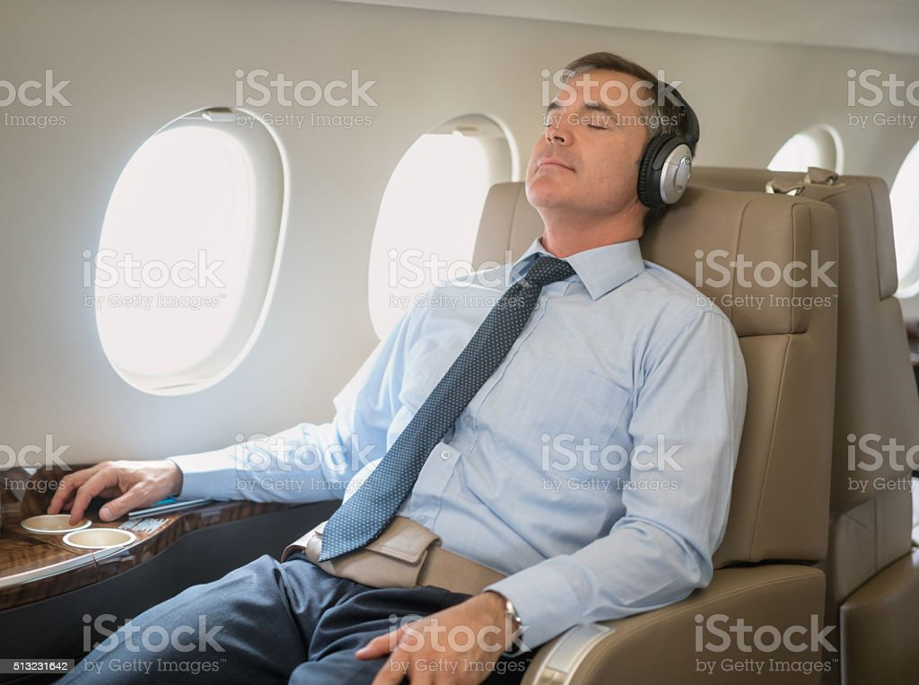 Man flying and relaxing in business class stock photo